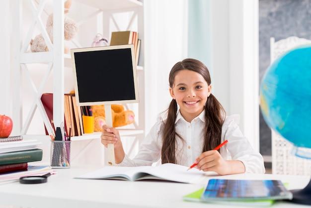 Feliz, schoolgirl, em, uniforme, estudar, em, sala aula Foto gratuita