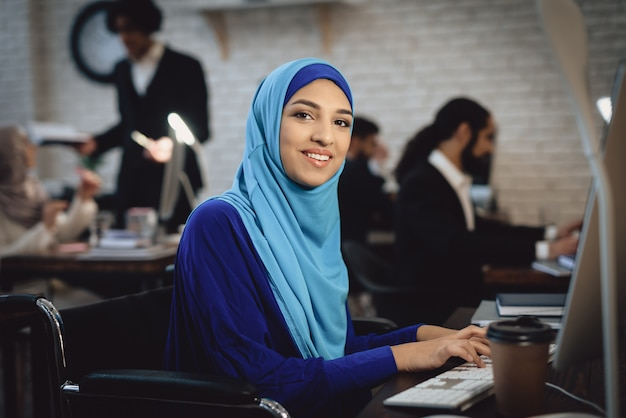 Feliz senhora árabe em cadeira de rodas trabalha no computador. Foto Premium