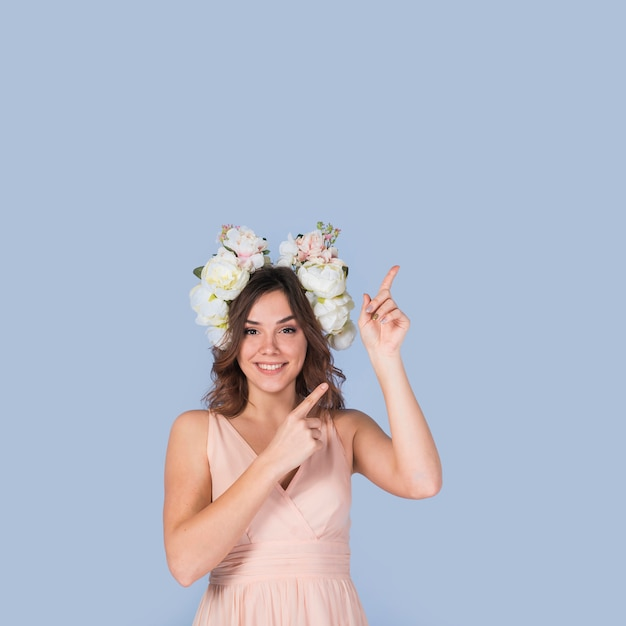 Feliz, senhora jovem, em, vestido, com, branca, grinalda, apontar, cima Foto gratuita