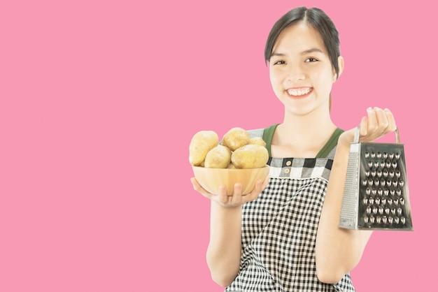 Feliz senhora segurando coisas de cozinha sobre fundo de espaço de cópia Foto gratuita