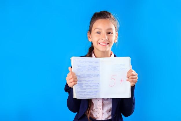 Feliz sorridente colegial de uniforme, segurando e mostrando o notebook com excelentes resultados de teste ou exame Foto Premium