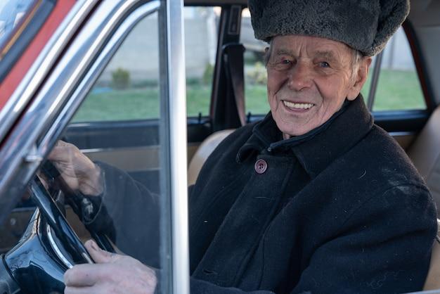 Feliz sorridente velho casaco preto dirigindo carro retrô, mantém as mãos no volante e olhando para a câmera Foto Premium
