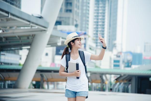 Feliz, sorrindo, estudante asiático, menina, com, mochila, em, cidade, fundo Foto gratuita