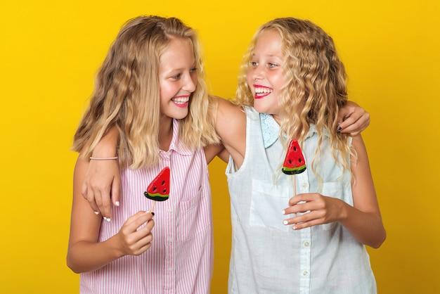 Feliz sorrindo irmãs gêmeas abraçando e rindo Foto Premium