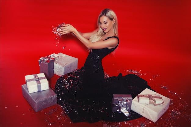 Feliz sorrindo mulher loira de vestido preto longo com caixas de presente e confetes caindo sobre o fundo vermelho isolado Foto Premium