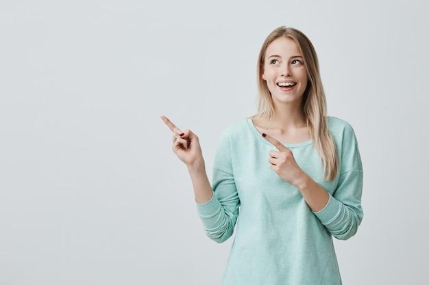 Feliz surpresa loira jovem fêmea sorrindo amplamente, apontando os dedos para longe, mostrando algo interessante e emocionante Foto gratuita