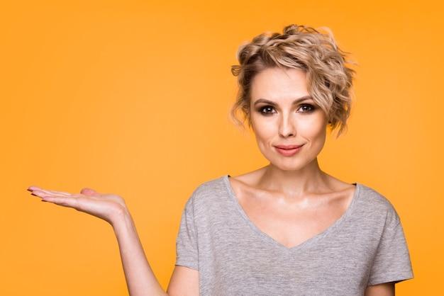 Feliz surpresa loira jovem sorrindo amplamente para a câmera, apontando os dedos para longe Foto Premium
