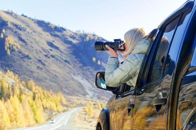 Feliz turista viajando na zona rural. mulher de turista em uma janela aberta de um auto carro tirando fotografia. blogger usando o conceito de conteúdo hobby, aproveite a viagem. Foto Premium