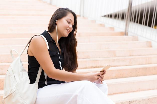 Feliz universitária relaxada ouvindo música no celular Foto gratuita