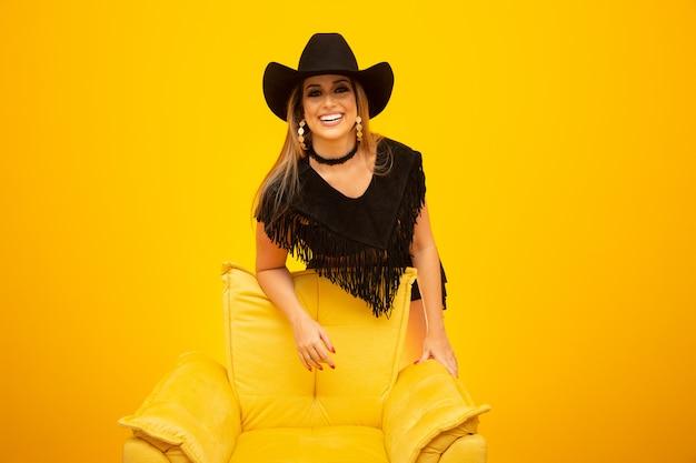Feliz vaqueira sexy em fundo amarelo Foto Premium
