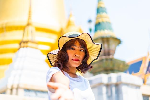 Feliz viagem asiática mulher no templo na tailândia Foto Premium