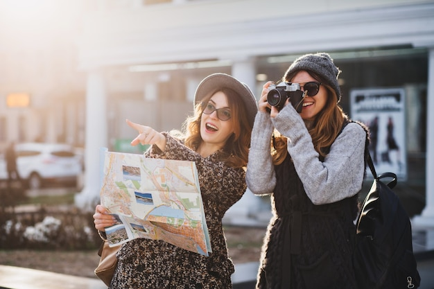 Feliz viagem juntos de duas mulheres elegantes no ensolarado centro da cidade. jovens mulheres alegres expressando positividade, usando mapa, férias com bolsas, câmera, fazer foto, emoções alegres, ótimo humor. Foto gratuita