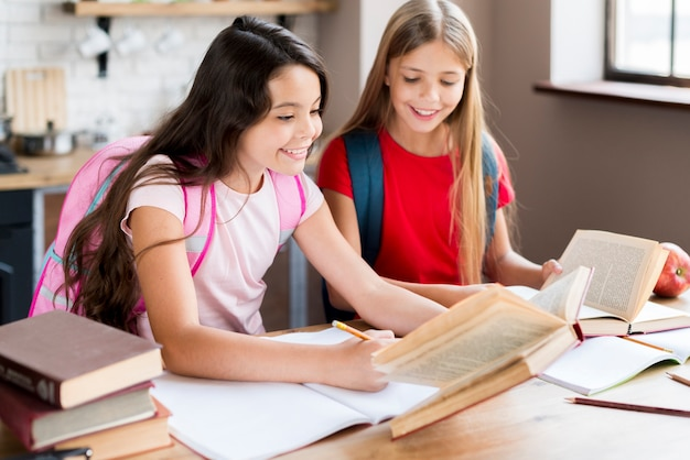 Felizes alunas com mochilas sentado na mesa e exercício em sala de aula Foto gratuita