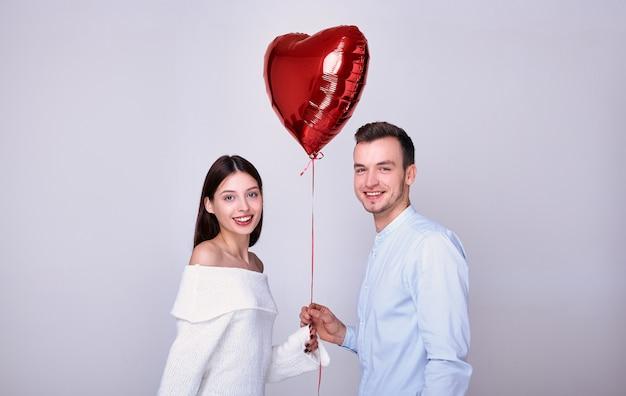 Felizes amantes com um balão vermelho em forma de coração. Foto Premium