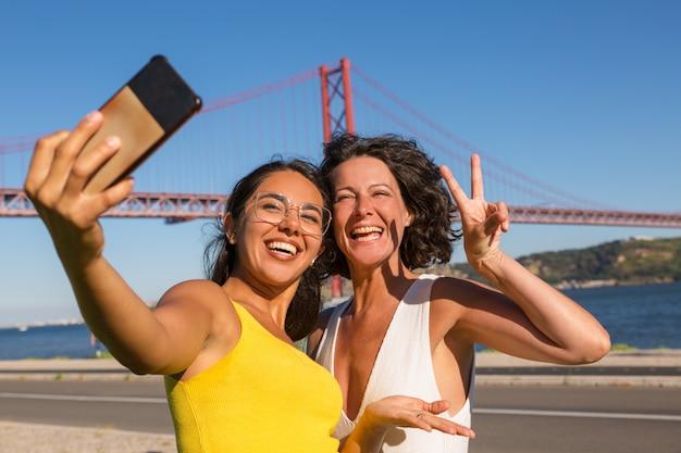 Felizes amigas posando para selfie Foto gratuita