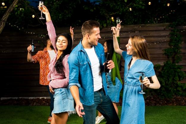 Felizes amigos dançando juntos com bebidas Foto gratuita