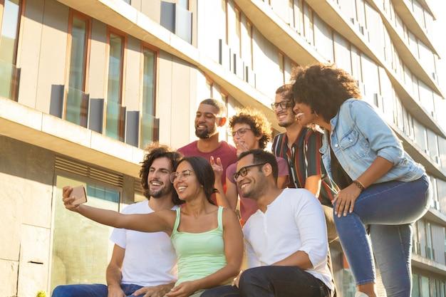 Felizes amigos multiétnicas felizes tomando selfie de grupo Foto gratuita