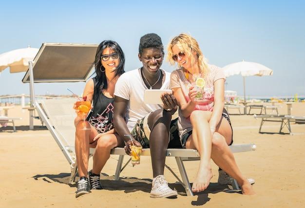 Felizes amigos multirraciais beber cocktails com tablet na praia Foto Premium