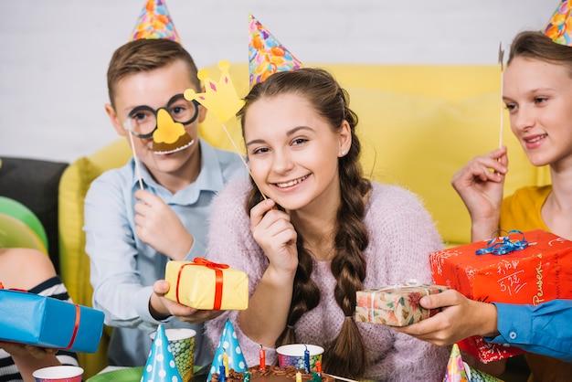 Felizes amigos segurando adereços na mão dando presentes para o adolescente sorridente Foto gratuita