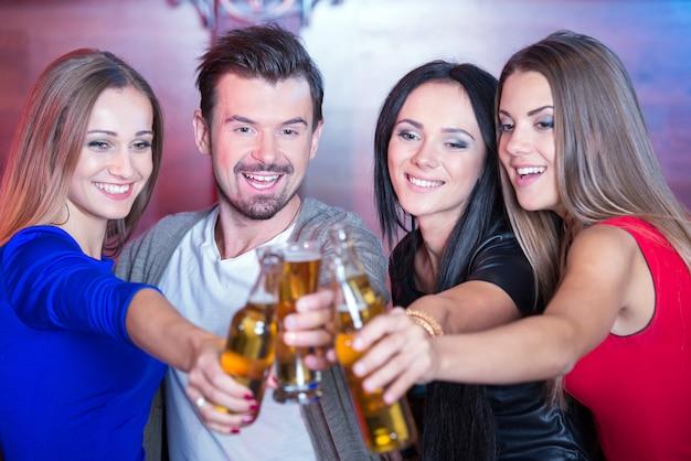 Felizes amigos segurando copos com cocktails no bar. Foto Premium