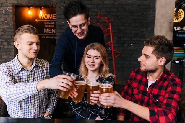 Felizes amigos tilintando os copos de cerveja no restaurante Foto gratuita