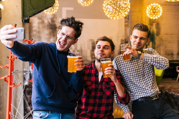 Felizes amigos tomando o selfie no celular segurando os copos de cerveja Foto gratuita