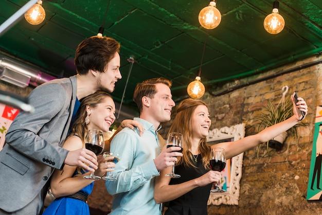 Felizes amigos tomando selfie no celular no restaurante bar de cocktails Foto gratuita