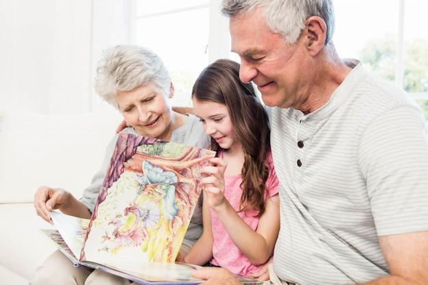 Felizes avós com neta lendo um livro no sofá Foto Premium
