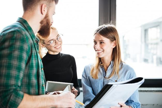 Felizes colegas no escritório falando um com o outro, segurando a pasta Foto gratuita