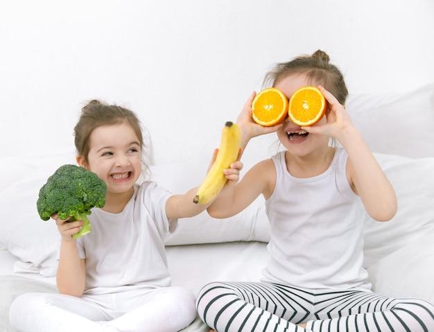 Felizes dois filhos bonitos brincam com frutas e vegetais sobre um fundo claro. alimentação saudável para crianças. Foto gratuita