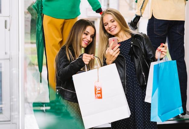 Felizes femininos amigos apreciando as compras perto da vitrine Foto gratuita