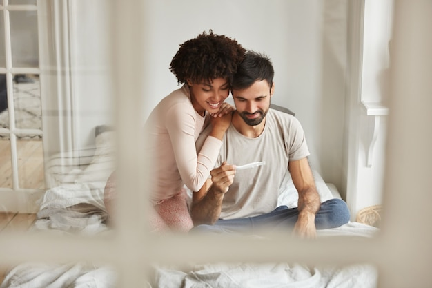 Felizes futuros pais de raça mista olham com alegria para o teste de gravidez, regozijam-se com as notícias positivas sobre a gravidez, sentem-se juntos na cama contra o interior doméstico. Foto gratuita