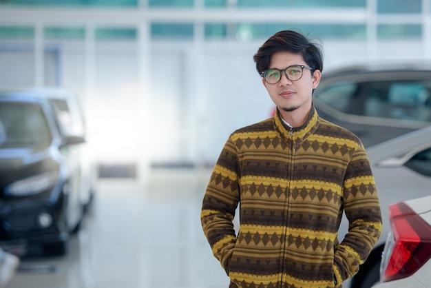 Felizes homens asiáticos que compram carros novos em salas de exposição e clientes satisfeitos acabam de comprar carros em concessionárias. Foto Premium