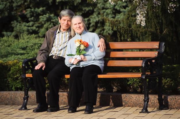 Felizes idosos felizes sentado no parque primavera Foto Premium