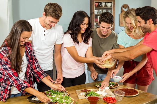 Felizes jovens amigos a cozinhar comida na cozinha em casa Foto Premium