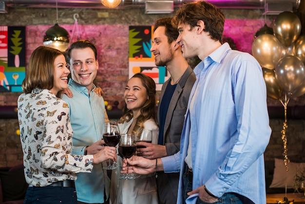 Felizes jovens amigos comemorando e brindando vinho no bar Foto gratuita