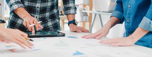 Felizes jovens empresários e empresárias da ásia reunindo-se para debater idéias sobre novos colegas de projeto de papelada trabalhando juntos, planejando uma estratégia de sucesso, e desfrutar do trabalho em equipe em um pequeno escritório moderno. Foto gratuita