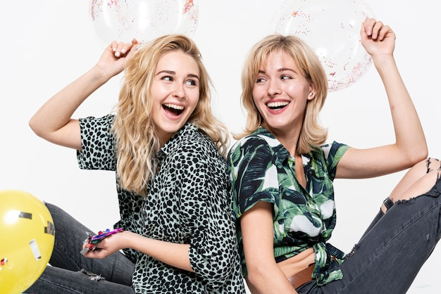 Felizes mulheres loiras segurando confetes Foto gratuita