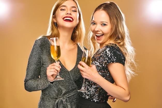Felizes mulheres sorridentes em elegantes vestidos glamourosos com taças de champanhe na parede dourada Foto gratuita