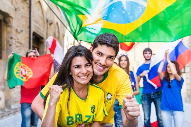 Felizes partidários brasileiros casal comemorando a vitória Foto Premium