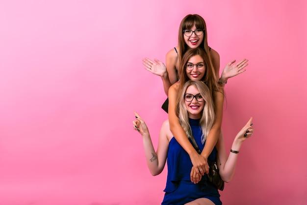 Felizes três garotas se abraçando e se divertindo juntas, emoções positivas e loucas, objetivos de amizade, óculos transparentes, roupas brilhantes e espaço rosa. Foto gratuita