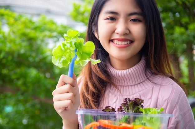 Fêmea adolescente nova com vegetais de salada Foto gratuita