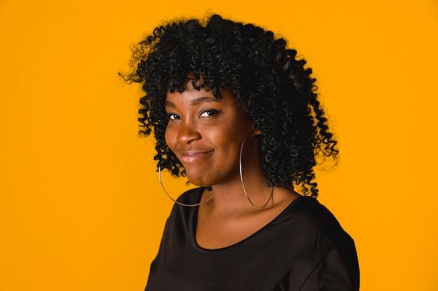 Fêmea americana africana engraçada no estúdio com fundo brilhante Foto gratuita