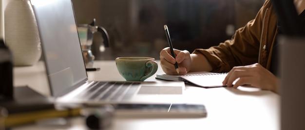 Fêmea, anotando-se no livro de agenda em branco na mesa branca com mock-se laptop e suprimentos no studio Foto Premium