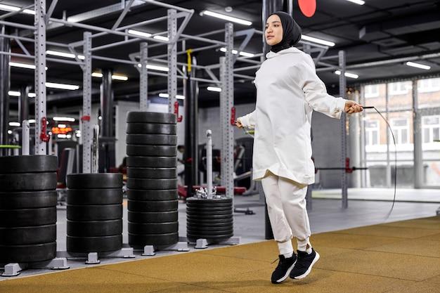 Fêmea árabe em treinamento de hijab com pular corda, fêmea forte magro envolvida em esportes, academia moderna, conceito de fitness Foto Premium