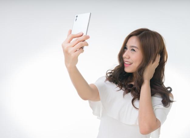 Fêmea asiática atrativa nova que toma o selfie, no branco Foto Premium