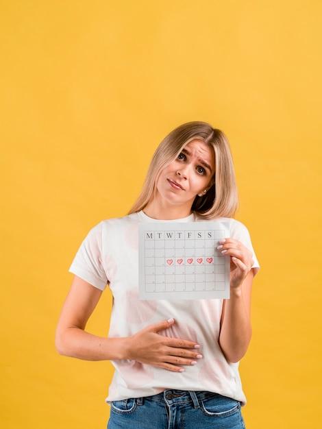 Fêmea coloca a mão no abdômen e mostrando o calendário do período Foto gratuita