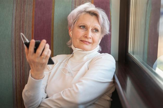 Fêmea de alto ângulo com telefone na mão Foto gratuita