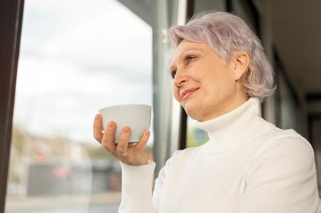 Fêmea de ângulo baixo com uma xícara de café olhando na janela Foto gratuita