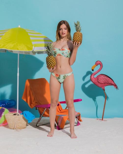 Fêmea de biquíni segurando frutas exóticas Foto gratuita